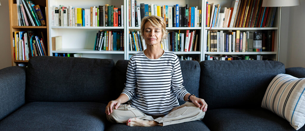 Woman sitting in a yoga pose with her eyes closed sitting on a couch in a home library